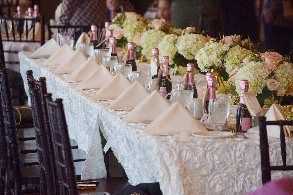 Wedding Reception Table With White Floral Table Cloth And Flowers